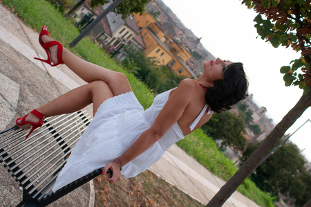 Portrait of a dark haired lady sitting on a bench in a city park. Very ironic and sensual. Wearing a white dress, red necklace, red shoes with heels. Happy and very playful and mischievous.