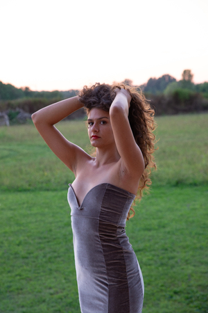 Close-up of girl with long wavy brown hair. Elegant dress in anthracite color. Warm sunlight at sunset. Naked shoulders and low-cut dress on the chest. Green background of a lawn
