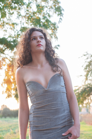 Close-up of a girl with long wavy brown hair. Elegant dress in anthracite color. Warm sunlight at sunset. Naked shoulders and low-cut dress on the chest. Brown eyes.