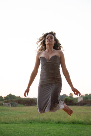 Girl jumping in the wind. Elegant dress in anthracite color. Warm sunlight at sunset. Naked shoulders and low-cut dress on the chest.