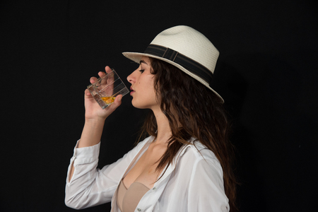 Young girl with brown hair and white hat on her head. With a glass of whiskey in your hand. Keep your white shirt open, very sensual. You can see a flesh-colored bra. Sensuality concept of young generations. Black background.