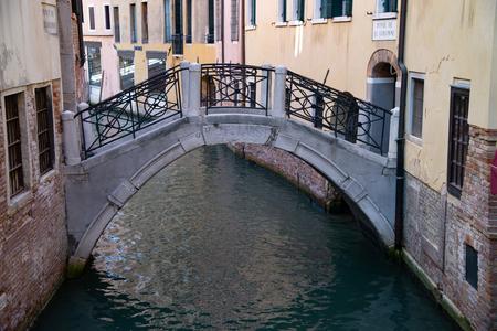 Bridge de le Colonne, on the Rio dei Fuseri. Calle dei Fuseri, Venice, Italy. Stone bridge; brick and stone structure, iron balustrade with oblique crosses and circles.