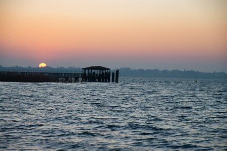 Beautiful sunset on the abandoned lake pier. Wooden structure for panoramic access to the lake. Sun on the horizon, silhouette of bridge with sunset. Colorful sky with clouds in the evening. 版權商用圖片
