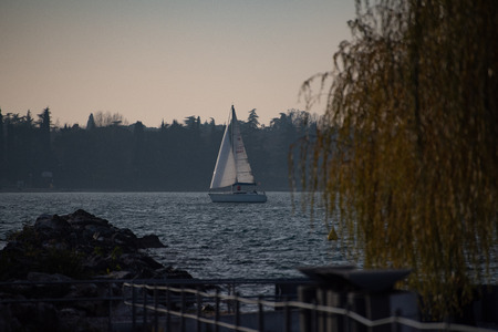 Sailboat in the middle of the lake. Profile of two shores of the lake with trees and houses.