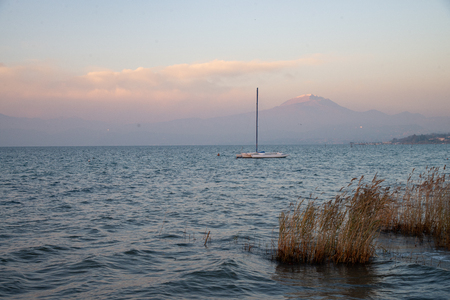 A winter lake with moored sailboat. Sky with pink clouds and warm evening light. Reeds on the shore. Background mountains profile. 版權商用圖片