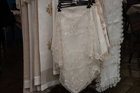 Tablecloths colored lace curtains hung and offered for sale. Assortment of lace and embroidery. Souvenir shop in Burano. Venice. Italy. The famous Burano lace is made by local artisans.