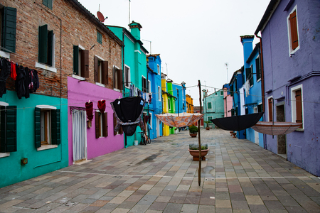 Cloths and umbrellas in the colorful houses of the island of Burano near Venice, Italy.