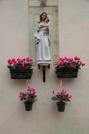Small external altar with Madonna with child and flower pots. Religious worship and tradition. Statue with vases of cyclamen flowers. Foto de archivo
