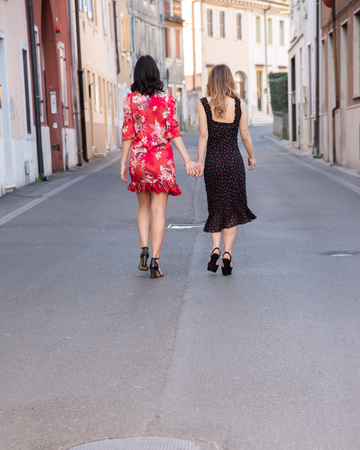 Full-length portrait from behind two friends, one blonde and the other brunette. Breathe a full sense and enjoy freedom. They are holding hands in the middle of the street. Concept of friendship 写真素材 - 121449108