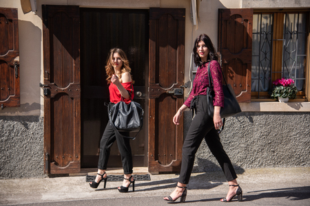 Two female friends are walking along the street. The other brunette in a red lace shirt and black bra with black pants. In the background door and window of a house.