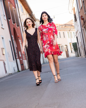 Full-length portrait of two friends, a blonde in a black dress and the other brunette in a red dress. Breathe a full sense and enjoy freedom. They are holding hands in the middle of the street. Concept of friendship. 写真素材