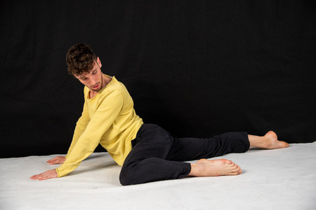 Male dancer with black trousers and yellow jersey on a black background. The young attractive man shows the poses in yoga.