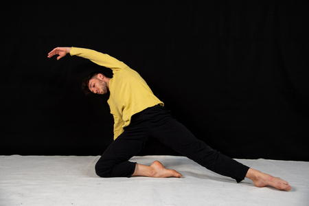 Male dancer with black trousers and yellow t-shirt, practicing in the studio on a black background. The attractive young man shows modern dance poses.