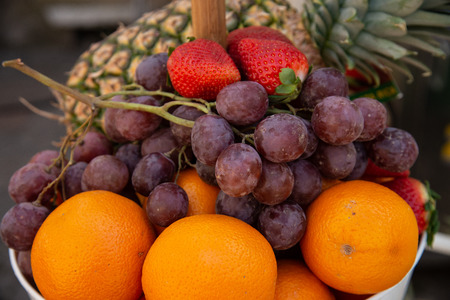 Fruit basket with red strawberries, grapes, pineapple, oranges. Fruit with high nutritional value, ready to be sold at the table at lunch.