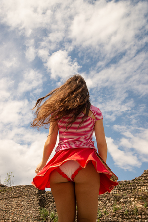 Young girl dressed in a red skirt and white striped T-shirt outdoors dancing around her skirt. Concept of freedom and movement against the blue sky with white clouds. 免版税图像