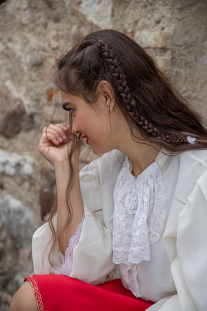 Very sweet girl sitting outside. Concept of child's play with teenage malice. Hair with braid. Photographed outdoors, concept of melancholy. Country of Castellaro Lagusello, Monzambano, Mantua, Italy, Europe. Imagens