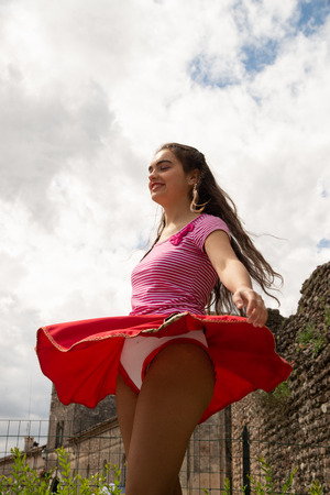 Young girl dressed in a red skirt and white striped T-shirt outdoors dancing around her skirt. Concept of freedom and movement against the blue sky with white clouds. Фото со стока