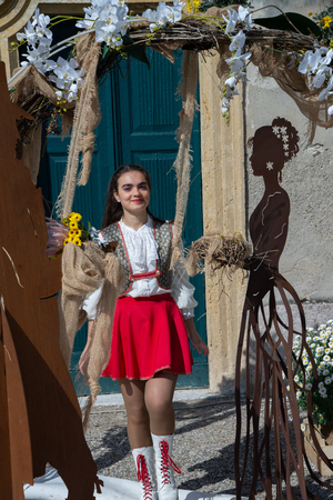 Girl wearing a uniform, outdoors, portrayed among a metal figure marriage concept. Country of Castellaro Lagusello, Monzambano, Mantua, Italy, Europe. Show annual flower market. 版權商用圖片