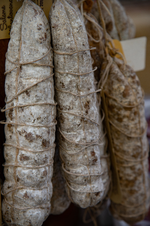 Salami hanging to be sold (Sopressa veronese, Italy). Sausage cured and seasoned pork.