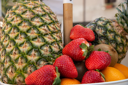 Fruit basket with red strawberries, pineapple, oranges. Fruit with high nutritional value, ready to be sold at the table at lunch.