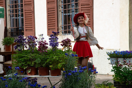 Girl wearing a uniform majorette, outdoors with flowers, portrait in hat with red feather and stick. Country of Castellaro Lagusello, Monzambano, Mantua, Italy, Europe. Show annual flower market. Stockfoto - 123074893