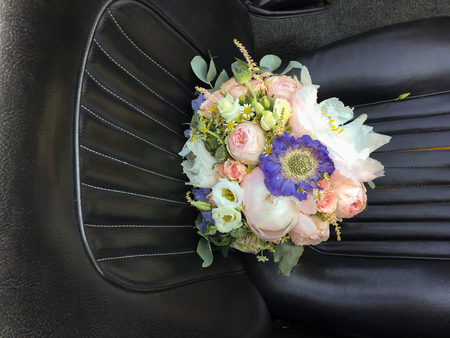 Bouquet of bridal flowers on the car seat. Beautiful rose flowers for the bride in a wedding.