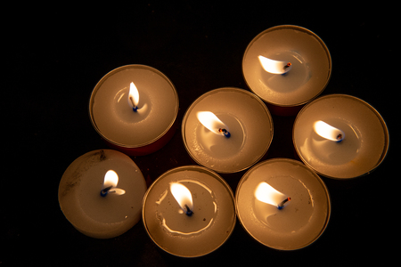 Group of votive candles in a church. Prayer candles in a church. Memorial candles in a church. Candles filled with yellow orange flame on a black background. Imagens