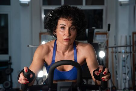 Woman seriously exercising in the gym using the exercise bike. Close up of a young muscular girl. Concept of fitness, sport, training, gym and lifestyle. Stock Photo