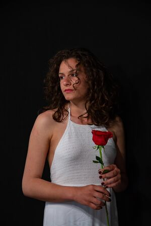 Half-length portrait of a beautiful brunette girl with curly, sexy hats in a white sleeveless tunic. He is holding a red rose. On a uniform black background, copy space. Stock fotó