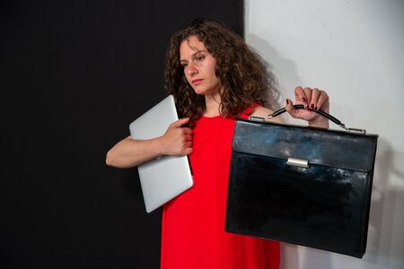 Young curly brunette woman with red dress, computer and black office bag, ready to go to the office. Concept of young modern girl in the morning before going to work. Black and white background.