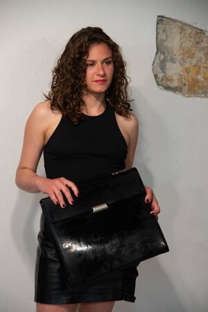 Half-length portrait of young curly brunette woman with black briefcase in her hand. Concept of girl ready to go to the office. She is wearing a black vest and a short skirt in black leather, smiling and sexy. Room white background. Stock fotó