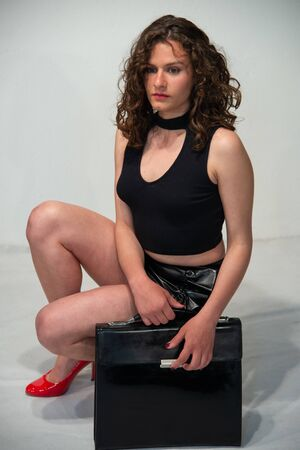 Young curly brunette woman ready to go to the office with her black bag. Sexy attitude, wear red heeled shoes. Dressed in a short black leather skirt and a short black sleeveless shirt. Room white background.