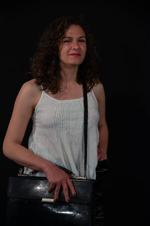 Young curly brunette woman with black shoulder bag. Concept of young sexy girl going to the office. He wears a white tank top, smiling and sexy. Black background.