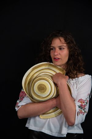Half-length portrait of a beautiful smiling curly brunette girl. She wears a white shirt and holds a straw hat with brown circles in his hands. On a uniform black background, copy space. Stock fotó