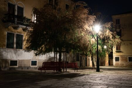 Night photography of a typical calle (small square) in Venice, Italy. In the foreground a wooden bench, trees and street lamps.