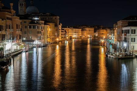 Night photo from the Rialto bridge in Venice, Italy. Overview of the Iron Shore and view of the Grand Canal illuminated by reflections on the water. View on the Vaporetti pier.