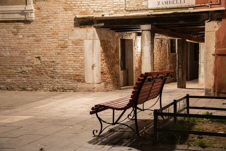 Night photography of the sotoportego Zambelli in Venice, Italy. In the foreground a wooden bench in Campo San Giacomo from the Orio