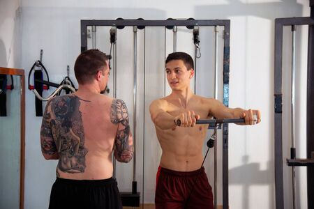Two young trainers doing exercises in the gym using tools to strengthen their muscles. Concept of fitness, sport, training, gym and lifestyle. Stock fotó