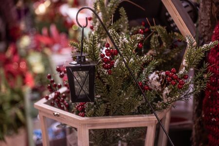 Sprigs of red berries among green leaves with lamp. Christmas decorations and for year-end celebrations.