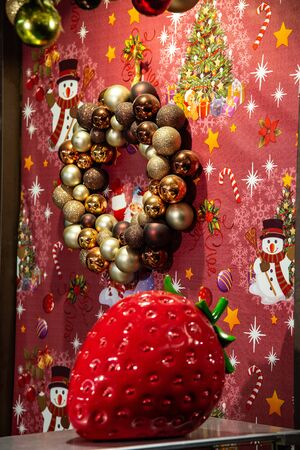 Showcase with decorative objects, large red strawberry and garland with decorative balls. Christmas decorations and year-end celebrations.