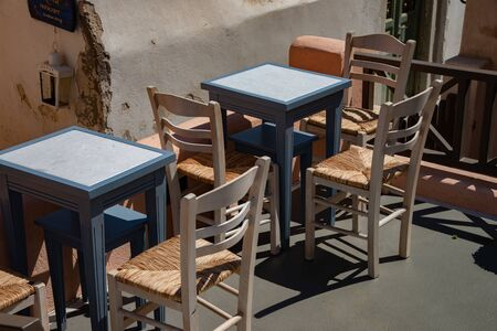 Colorful chairs and tables in typical Greek coffee. Outdoor cafe on a street Traditional Greek village on Santorini, Firestefani, Greece.