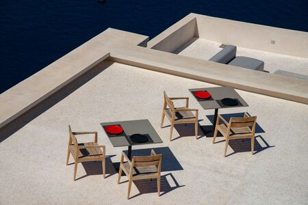 Typical terrace with tables and chairs for breakfast or coffee break on the island of Santorini, Greece, Europe. Color and design with a direct view of the gulf caldera. Stock fotó