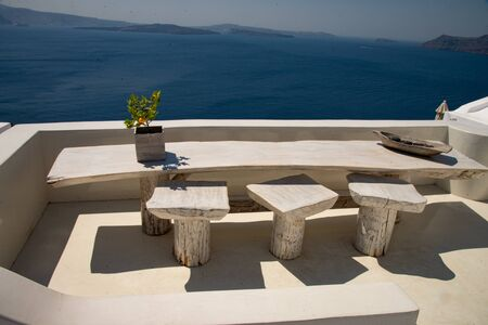 Typical stately terrace with solid wood table and chairs for breakfast or coffee break on the island of Santorini, Greece, in Oia. Color and design with a direct view of the gulf caldera and the island of Nea Kameni. Stock fotó