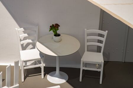 White chairs and tables in the typical Greek terrace. For breakfast or coffee break on the island of Santorini in Europe. Stock fotó