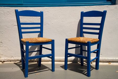 Two Greek-style blue straw chairs, Firestefani, Santorini island, Greece, Europe. Typical in taverns and outside cafes.