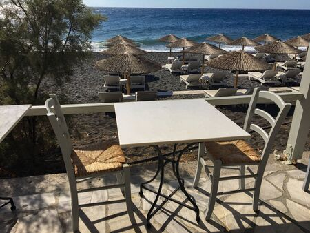 White chairs in the typical Greek restaurant along the sea. Outdoor venue on a street in Santorini, Kamari, Greece, overlooking the beach with umbrellas and sea. Stock fotó