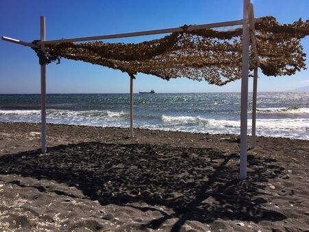Mega gazebo craft structure on a beach in Kamari in Santorini, Greece. The Aegean Sea, in the distance on the horizon in a large boat.