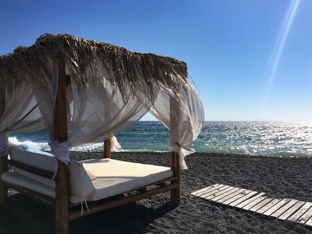 Mega gazebo with double bed on a beach in Santorini, Greece. External structure in wood, straw and fabric on the banks of the Aegean with reflections of the sun.