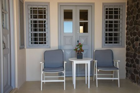 Small table with chairs, two windows and doors, characteristics of homes in Greece. Outdoors on the island of Santorini, in Kamari, Greece.