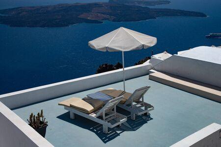 Deck chairs on the island of Santorini, Greece, Europe. View of the gulf caldera with the island of Nea Kameni. Stock fotó